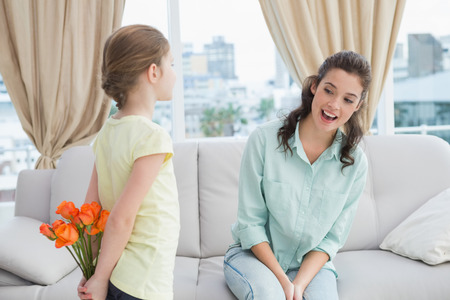 Cute girl hiding flowers from mother at home in the living room photo