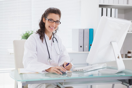 Smiling vet writing and using computer in medical office photo