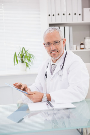 Smiling doctor using a tablet pc in medical office photo