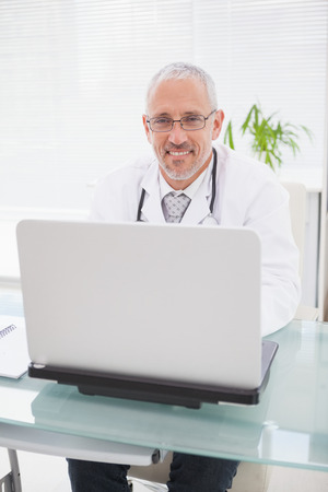 Smiling doctor using laptop in medical office