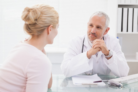 Patient consulting a happy doctor in medical office photo