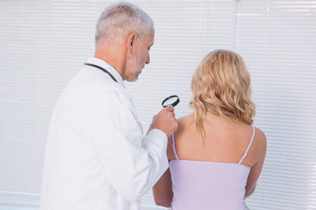 Doctor examining patient with magnifying glass in medical office photo
