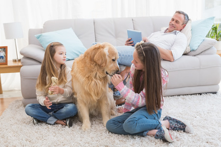 life at home:  Smiling sisters petting their golden retriever on rug at home in the living room