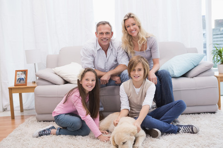 Smiling family with their pet yellow labrador on the rug at home in the living room photo