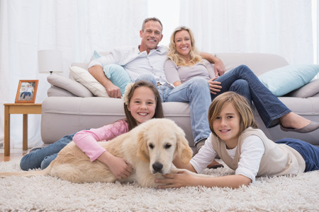 family indoors: Cute siblings playing with dog with their parent on the sofa at home in the living room