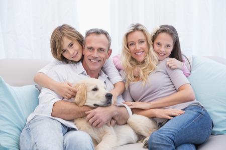 Nette Familie entspannt zusammen auf der Couch mit ihrem Hund zu Hause im Wohnzimmer