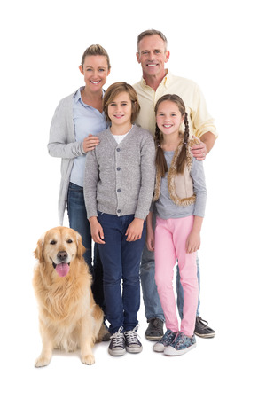 portrait of a women: Portrait of smiling family standing together with their dog on white background