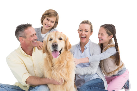 Portrait of smiling family sitting together with their dog on white background