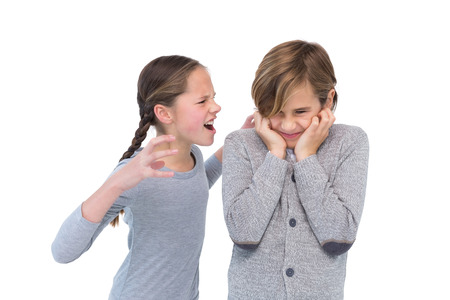 brother sister fight: Portrait of an unhappy girl screaming at her brother on white background Stock Photo