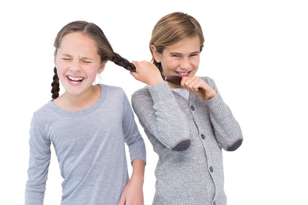 Angry young boy pulling sister hair in a fight on white background photo