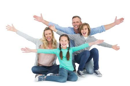 Cheering family with two children sitting on the floor on white background