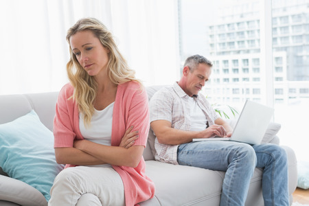 Unhappy couple are stern and having troubles at home in the living room photo