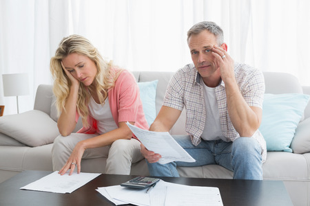 figuring: Worried couple calculating bills on the couch at home in the living room