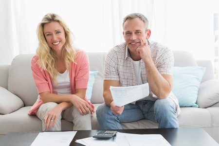 figuring: Couple doing their accounts sat in a couch at home in the living room