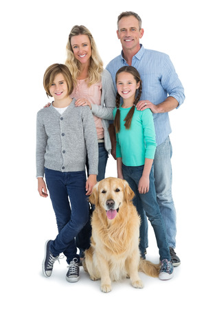 family with two children: Portrait of smiling family standing together with their dog on white background