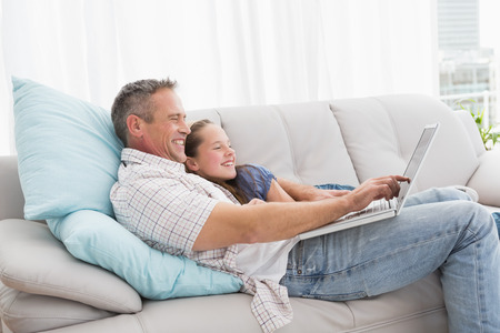 sitting room: Father with daughter relaxing on the couch using laptop at home in the living room