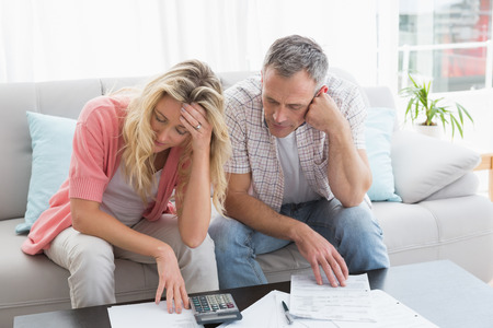 Worried couple calculating bills on the couch at home in the living room photo