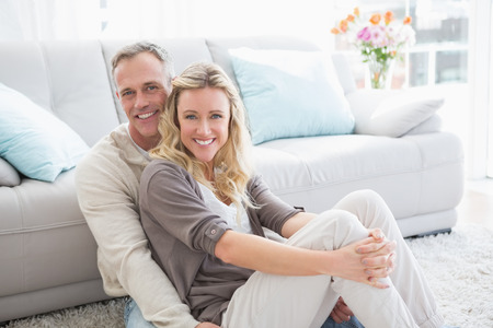 Happy casual couple sitting on rug smiling at camera at home in the living room Stok Fotoğraf