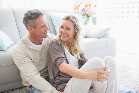 happy life: Happy casual couple sitting on rug at home in the living room