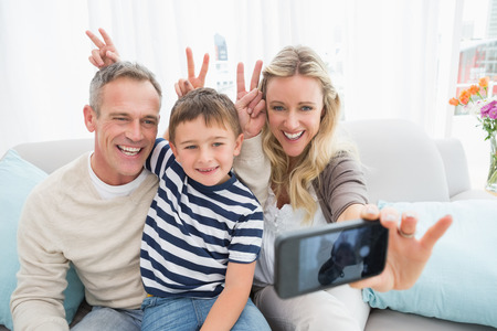 Cheerful family taking self pictures with a smartphone at home in the living room photo