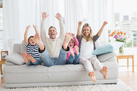 man couch: Family sitting on a couch and raising arms at home in the living room