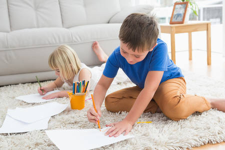 Smiling siblings drawing lying on the floor at home in the living room photo