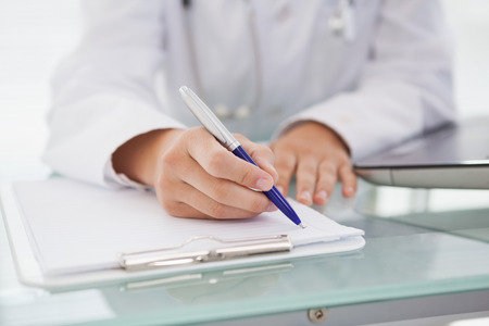 medical notes: Doctor writing down medical notes on clipboard Stock Photo