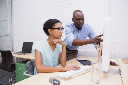 Man showing something to his colleague on the laptop in the office Stock Photo
