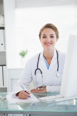 Doctor smiling as she takes notes in her office photo