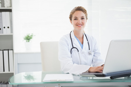 Doctor smiling as she types on her laptop photo