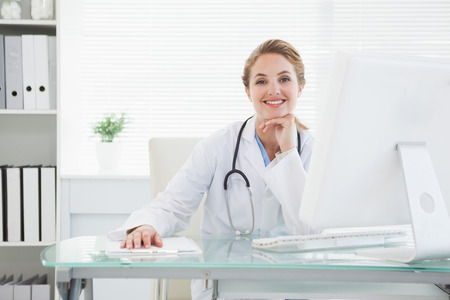 Doctor smiling at the camera in her office photo