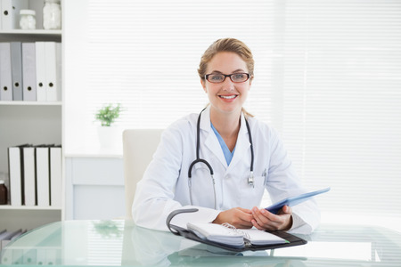 Doctor holding her tablet pc in her office photo