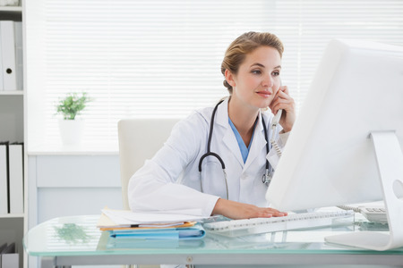 Doctor answering a telephone call in her office photo