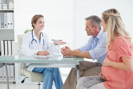 Happy couple talking to doctor about pregnancy photo