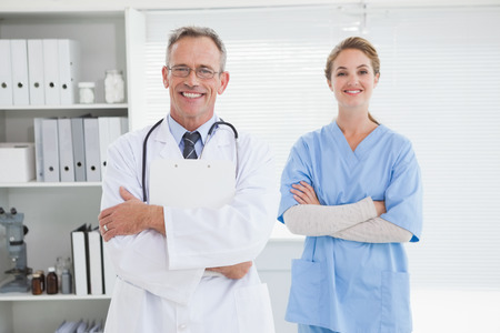 Smiling doctor with fellow co worker in his office photo