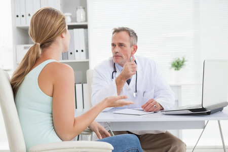 Concerned doctor talking to his patient in his office photo
