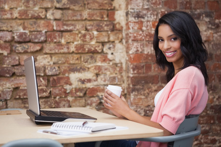 Smiling woman drinking coffee at her desk using laptop in the office photo