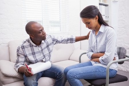 comforted: Worried woman being comforted by her therapist in the office Stock Photo