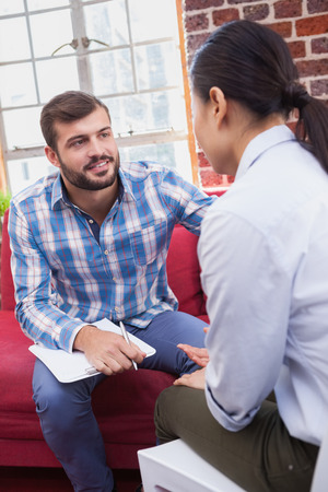 health problems: Therapist advising his listening patient on couch in office Stock Photo