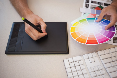 designer: Designer using graphics tablet and colour wheel in the office