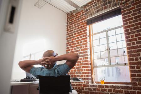 relajado: Casual de negocios recostado en la silla en la oficina