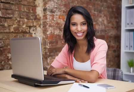 Happy woman using her laptop smiling at camera in the office photo