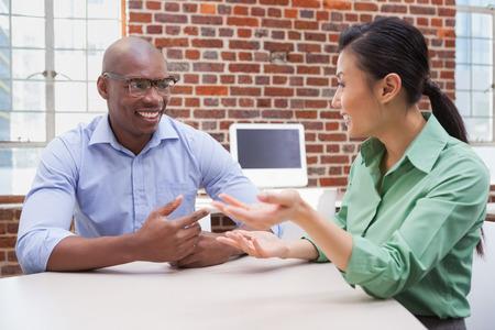 persone che parlano: Uomini d'affari casual parlando al tavolo e sorridente in ufficio