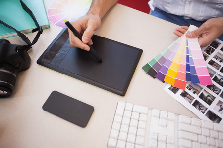 graphics tablet: Designer using graphics tablet and colour charts in the office Stock Photo