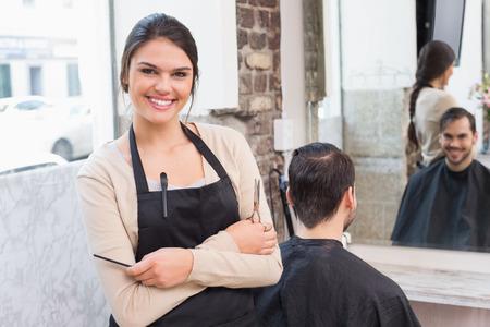 hair short: Bastante estilista sonriendo a la c�mara en la peluquer�a Foto de archivo