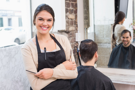 male beauty: Pretty hair stylist smiling at camera at the hair salon