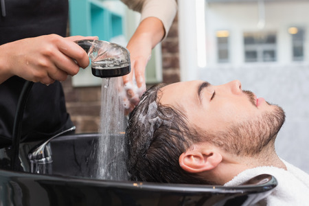 young adult men: Hair stylist washing mans hair at the hair salon