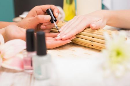 nail varnish: Nail technician giving customer a manicure at the beauty salon Stock Photo