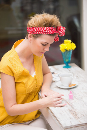 Pretty hipster painting her nails at wooden table photo