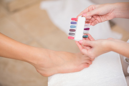 Beautician showing client nail colours at the beauty salon photo